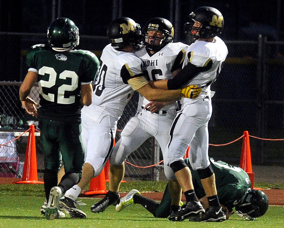 "Monarch High School's Jake Hummel, center, is hugged by teammates after tackling punter Brian Toles, at right, at the one yard line after a wild snap during a game on Thursday, Sept. 13, against Niwot High School at Longmont High School. Monarch won the game 53-12. For more photos of the game go to  <a href=""http://www.dailycamera.com"">http://www.dailycamera.com</a><br /> Jeremy Papasso/ Camera"