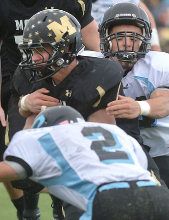 Monarch's Ethan Marks is tackled by Pueblo West's Cameron Barry (2) and Josh Casias during the state 4A semi-final game at Warrior Stadium in Lafayette on Saturday.<br /> <br /> November 24, 2012<br /> staff photo/ David R. Jennings