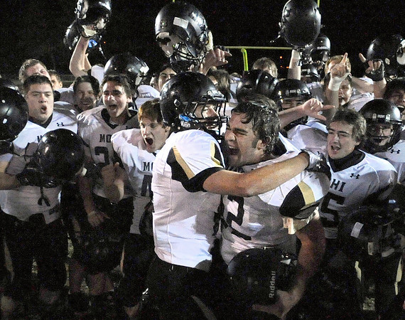 """Monarch High School junior Luke Yontz, left, hugs sophomore Tyler Bender while joining the victory celebration on Friday, Nov. 5, after defeating Wheat Ridge High School in a football game at Jeffco Stadium in Lakewood.<br /> Monarch defeated Wheat Ridge 26-14.<br /> For more photos go to  <a href=""""http://www.dailycamera.com"""">http://www.dailycamera.com</a><br /> Jeremy Papasso/ Camera"""