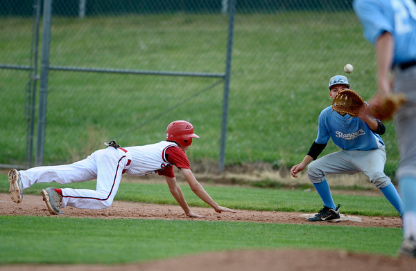 """Fairview's Ryan Madden slides to safety on first base at the bottom of the fourth inning on Friday, July 6, during a baseball game against Mountain Range at Fairview High School in Boulder. For more photos of the game go to <a href=""""http://www.dailycamera.com"""">http://www.dailycamera.com</a>"""