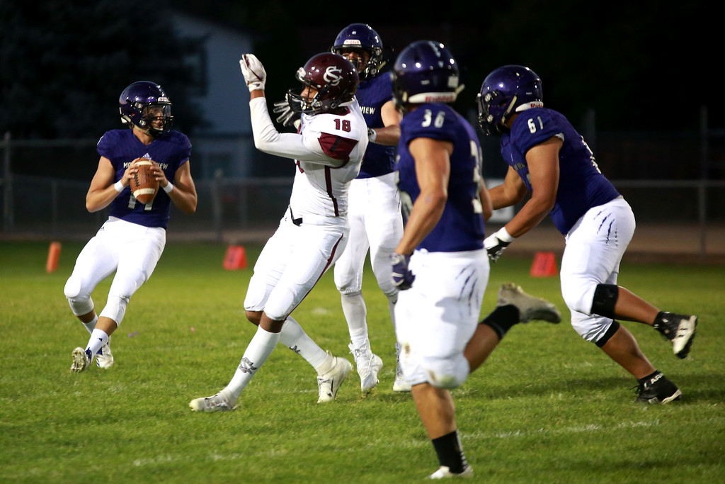 . Mountain View�s (11) Lukas Arthur looks for an opening with teammates (36) Tobin Armstrong and (61) Luke Hard as Silver Creek�s (18) Caleb Sedegan tires to block him on Friday night�s game on Sept. 21, 2018 at Patterson Stadium in Loveland. 
