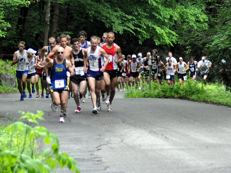 Just three minutes into the 49th Mt. Washington Road Race, runners were still tightly grouped. Leading here is Simon Gutierrez (#4), with eventual race winner Rickey Gates (#2) a few feet behind. Pictured to the left is North Conway's Kevin Tilton #11, who finished 19th.