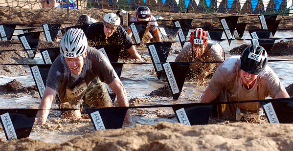 "A group of competitors make it through the last obstacle, the mud pit.<br /> The Muddy Buddy Ride and Run requires a 2-person team to finish a 6-7 mile course with 5 obstacles. One member will ride and one will run, but they need to finish together. The race was held at the Boulder Reservoir on Sunday.<br />  For more photos and a video, go to  <a href=""http://www.dailycamera.com"">http://www.dailycamera.com</a>.<br /> <br /> <br /> Cliff Grassmick / August 16, 2009"