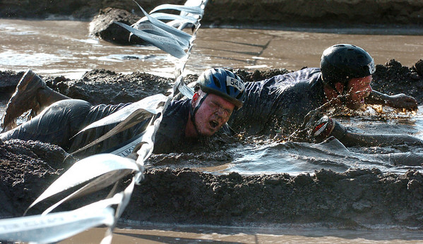 A pair of competitors make it through the last obstacle, the mud pit. The Muddy Buddy Ride and Run requires a 2-person team to finish a 6-7 mile course with 5 obstacles. One member will ride and one will run, but they need to finish together. The race was held at the Boulder Reservoir on Sunday.  For more photos and a video, go to www.dailycamera.com.   Cliff Grassmick / August 16, 2009