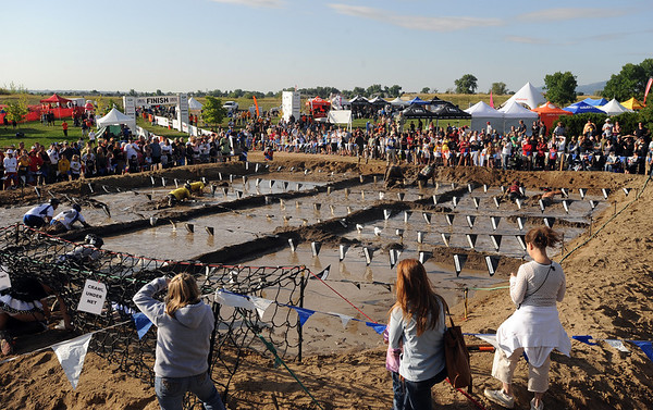 "The mud pit was the last and most fun obstacle.<br /> The Muddy Buddy Ride and Run requires a 2-person team to finish a 6-7 mile course with 5 obstacles. One member will ride and one will run, but they need to finish together. The race was held at the Boulder Reservoir on Sunday.<br />  For more photos and a video, go to  <a href=""http://www.dailycamera.com"">http://www.dailycamera.com</a>.<br /> <br /> <br /> Cliff Grassmick / August 16, 2009"