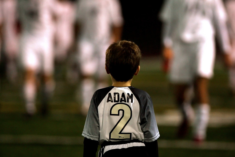 """Dreaming""<br /> <br /> A five-year old contemplates the High School varsity team as they walk back to start the second half of their game.  Taken under field lights in the evening (September 2007)."