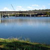 Construction of the new bridge behind the old one over Lake Marble Falls