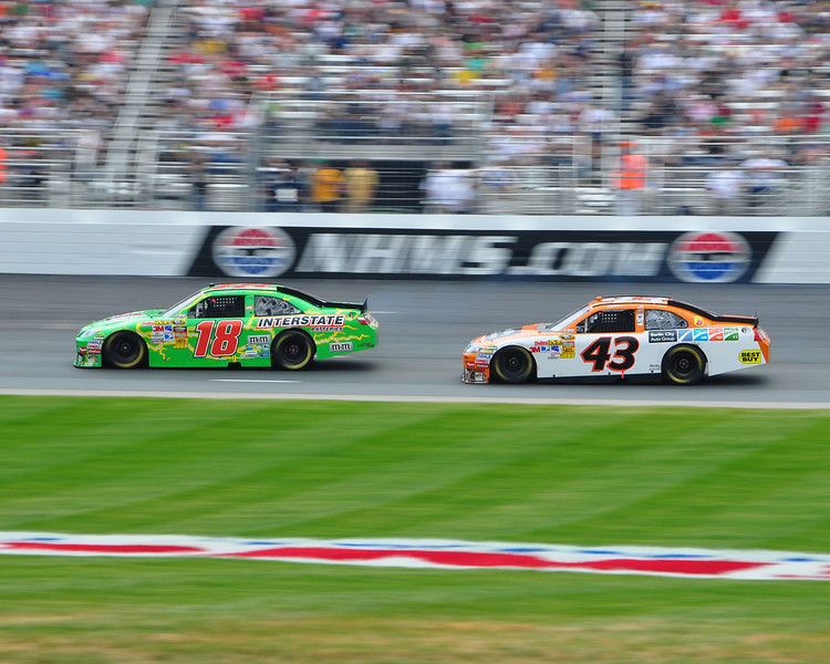The NASCAR Sprint Cup Series came to New Hampshire Motor Speedway, in Loudon, on June 27th, 2010, for The Lennox Industrial Tools 301. Kyle Busch (#18), driving the Interstate Batteries/Joe Gibbs Racing Toyota, stays just ahead of A.J. Allmendinger, driver of the Berlin City Auto Group/Richard Petty Motorsports Ford.