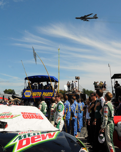A B-52 flies overhead, as NASCAR Sprint Cup Series drivers, owners, and crew members, stand for the National Anthem, prior to the start of The Sylvania 300, at New Hampshire Motor Speedway, in Loudon, NH. on September 25th, 2011.