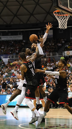 Montrezl Harrell drives through three Rockets in a preseason game against the Houston Rockets on October 3, 2019, at the Stan Sheriff Center in Honolulu, Hawaii.