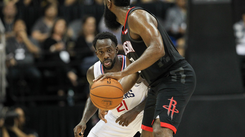 Clippers guard Patrick Beverley keeps an eye on the ball as James Harden dribbles during a preseason game against the Houston Rockets on October 3, 2019, at the Stan Sheriff Center in Honolulu, Hawaii.