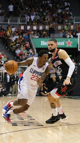 Lou Williams of the Los Angeles Clippers drives on Austin Rivers of the Houston Rockets during a preseason game against the Houston Rockets on October 3, 2019, at the Stan Sheriff Center in Honolulu, Hawaii.