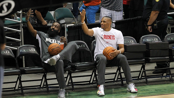 James Harden and Russell Westbrook pose on the bench before a preseason game against the Los Angeles Clippers on October 3, 2019, at the Stan Sheriff Center in Honolulu, Hawaii.