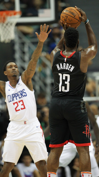 James Harden shoots a three over Lou Williams during a preseason game against the Los Angeles Clippers on October 3, 2019, at the Stan Sheriff Center in Honolulu, Hawaii.