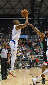 Rodney McGruder of the Los Angeles Clippers shoots a jumper over P.J. Tucker in a preseason game against the Houston Rockets on October 3, 2019, at the Stan Sheriff Center in Honolulu, Hawaii.