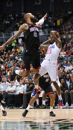 Lou Williams hangs in the air against Tyson Chandler in a preseason game against the Houston Rockets on October 3, 2019, at the Stan Sheriff Center in Honolulu, Hawaii.