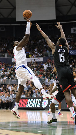 Montrezl Harrell fades away from Clint Capela during a preseason game against the Houston Rockets on October 3, 2019, at the Stan Sheriff Center in Honolulu, Hawaii.
