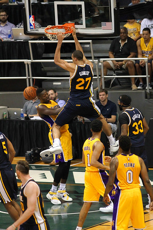 Jazz center Rudy Gobert (27) hangs on the rim after a dunk against the Lakers during an NBA preseason game at the Stan Sheriff Center, Honolulu, HI on October 04, 2015.