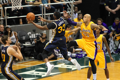 Utah Jazz forward Trevor Booker (33) drives to the rim as Los Angeles Lakers center Robert Sacre (50) defends in an NBA preseason game at the Stan Sheriff Center, Honolulu, HI on October 04, 2015.