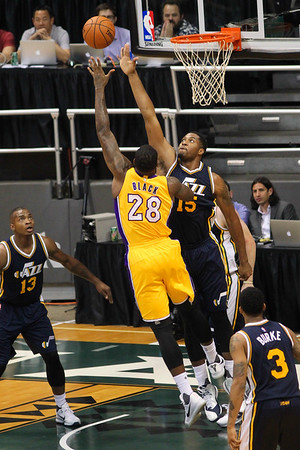 Tarik Black (28) of the Los Angeles Lakers shoots a jump hook over the outstretched arm of Derrick Favors (15) of the Utah Jazz Kobe Bryant (24) of the Los Angeles Lakers looks to drive on Utah Jazz forward Joe Ingles (2) during an NBA preseason game at the Stan Sheriff Center, Honolulu, HI on October 04, 2015.