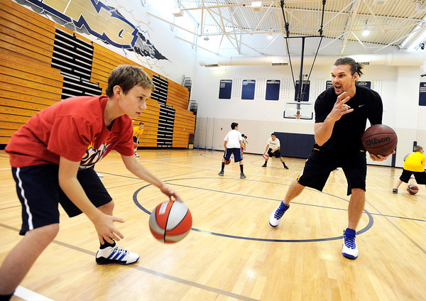"Thomas Bounds, 11, at left, gets dribbling tips from NBA player Louis Amundson on Monday, June 18, during a basketball camp at Legacy High School in Broomfield. For a video of the camp and interview with Amundson go to  <a href=""http://www.dailycamera.com"">http://www.dailycamera.com</a><br /> Jeremy Papasso/ Boulder Daily Camera"