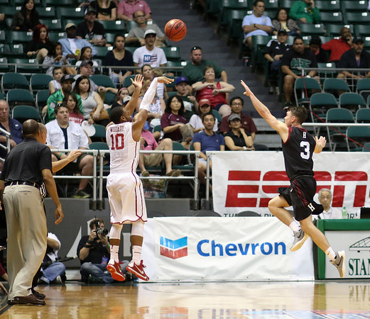 Oklahoma guard Jordan Woodard shoots a three from the wing as Harvard guard Tommy McCarthy defends in the championship game of the 2015 Diamond Head Classic at the Stan Sheriff Center, Honolulu, HI on December 25, 2015. Photo: Brandon Flores.