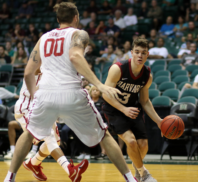 Harvard guard Tommy McCarthy drives as Oklahoma's Ryan Spangler defends in the championship game of the 2015 Diamond Head Classic at the Stan Sheriff Center, Honolulu, HI on December 25, 2015. Photo: Brandon Flores.