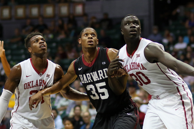 Harvard's Agunwa Okolie (35) watches a free throw between Oklahoma's Buddy Hield (24) and Akolda Manyang (30) in the championship game of the Diamond Head Classic at the Stan Sheriff Center, Honolulu, HI on December 25, 2015. Photo: Brandon Flores.