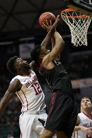 Harvard's Zena Edosomwan makes a move to the hoop against the defense of Oklahoma's Khadeem Lattin in the championship game of the Diamond Head Classic at the Stan Sheriff Center, Honolulu, HI on December 25, 2015. Photo: Brandon Flores.