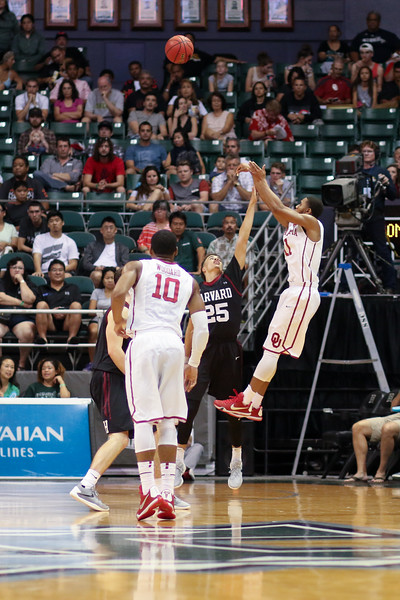 Oklahoma's Isaiah Cousins (11) shoots over the outstretched arm of Harvard's Corey Johnson (25) in the championship game of the Diamond Head Classic at the Stan Sheriff Center, Honolulu, HI on December 25, 2015. Photo: Brandon Flores.
