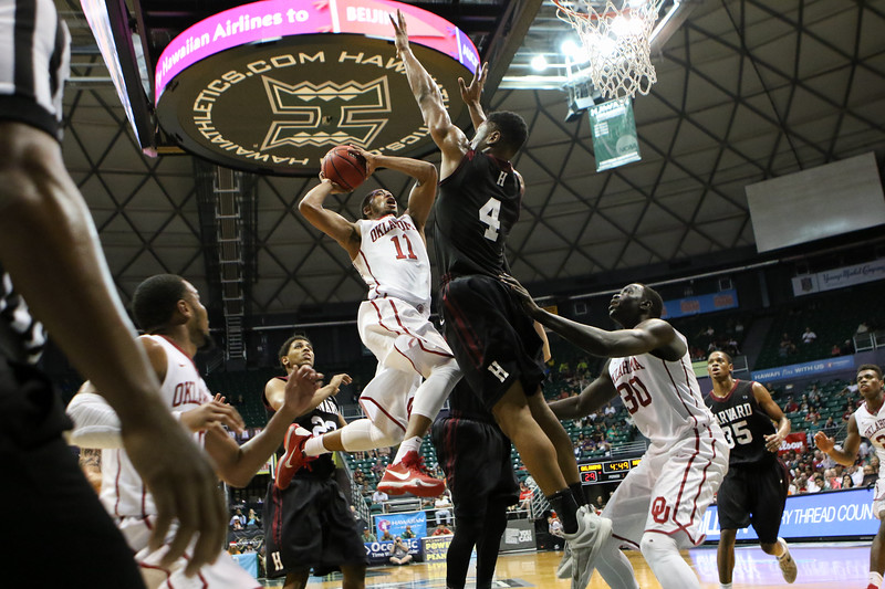 Oklahoma's Isaiah Cousins hangs in the air as Harvard's Zena Edosomwan defends in the championship game of the Diamond Head Classic at the Stan Sheriff Center, Honolulu, HI on December 25, 2015. Photo: Brandon Flores.