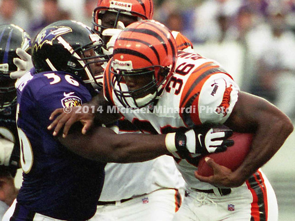 BALTIMORE, MD - SEPTEMBER 24: Half Back Brandon Bennett #36 of the Cincinnati Bengals carries the ball through the Baltimore Ravens front line for some extra yardage but then is tackled by Linebacker Anthony Davis #56 and Defensive End Michael McCrary #99 of the Baltimore Ravens in a NFL game at PSINet Stadium on September 24, 2000 in Baltimore, Maryland. The Ravens won the game 37-0. (Photo by Michael J. Minardi) *** Local Caption *** Brandon Bennett;Anthony Davis;Michael McCrary