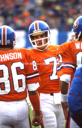 DENVER, CO - NOVEMBER 25: QB John Elway #7 of the Denver Broncos talks to fellow teammates before his first Quarterback appearance in a NFL game against the Seattle Seahawks at Denver mile high stadium. Seattle won 27 to 24. (Photo by Michael J. Minardi) *** Local Caption *** John Elway