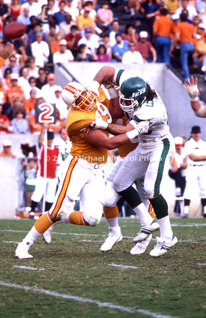 TAMPA, FL - DECEMBER, 16; Defensive End Mark Gastineau #99 of the New York Jets collides with Offensive Tackle Kenneth Kaplan # 79 of the Tampa Bay Buccaneers during a game in Tampa Stadium on December 16, 1984. The Bucs won 41-21. (Photo by Michael Minardi) *** Local Caption *** Mark Gastineau;Kenneth Kaplan
