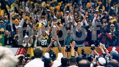 Green Bay Packers fans cheer as Hall of Famer Reggie White shows them their Lombardi Trophy after the Packers beat the Patriots in Super Bowl XXXI