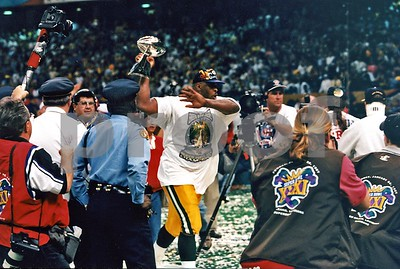 Green Bay Packers Great Reggie White runs around New Orleans Superdome stadium with the Lombardi Trophy after Packers beat the NE Pats for their 12th NFL Championship and 3rd Super Bowl Victory.
