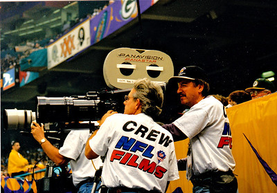 Chuck Cohen films Super Bowl XXXI in New Orleans for NFL Films,  as his camera assistand Ron Vargas racks focus.  Camera position is behind the end zone on the field.