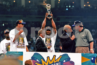 Reggie White hoists the Lombardi Trophy after the Green Bay Packers beat the NE Patriots in the 1996 Super Bowl.  (L to R) MVP Desmond Howard, Brett Favre, Packers President Bob Harlan, and Terry Bradshaw interviewing head coach Mike Holmgren.