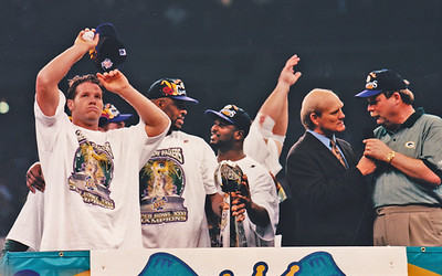 A relieved Brett Favre shares podium moment at Super Bowl XXXI with Reggie White talking to LeRoy Butler while both hold the Lombardi Trophy, and Terry Bradshaw interviews head coach Mike Holmgren.