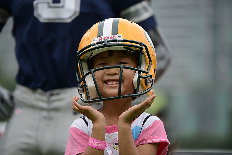 NFL Home Field Guangzhou - Week 9 - Young fan tries on a Green Back Packers helmet