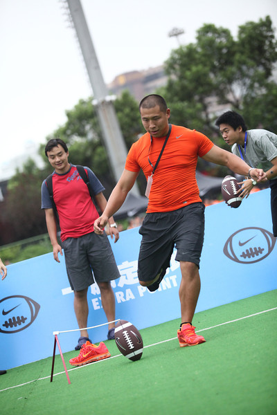 NFL player prospect, Ding Long (placekicker), shows visitors how to kick a field goal