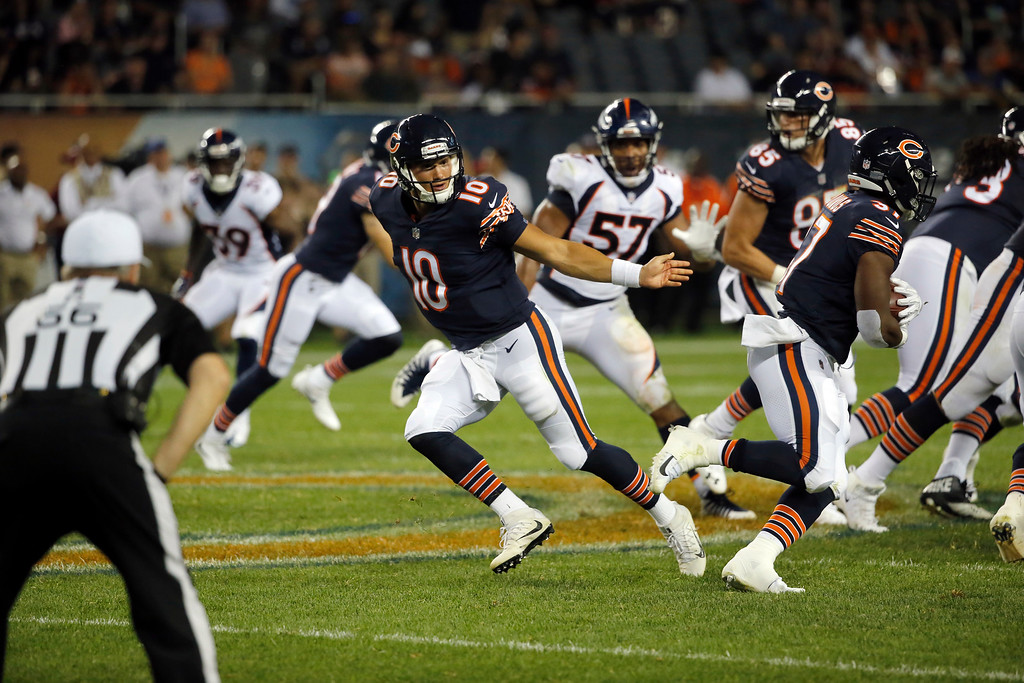 . Chicago Bears quarterback Mitchell Trubisky (10) hands off the ball to running back Joel Bouagnon (37) during the second half of an NFL preseason football game against the Denver Broncos, Thursday, Aug. 10, 2017, in Chicago. (AP Photo/Charles Rex Arbogast)