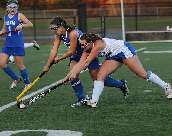 CARL RUSSO/Staff photo. Winnacunnet High School defeated Salem High School 2-0 in field hockey tournament action Thursday night. Salem's captain, Danielle Donovan (center) battles for the ball with Winnacunnet's Ashley Harnum. 10/25/2012.