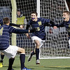 MARY SCHWALM/Staff photo. Windham players Casey Coupe (left), David Carbonello (15) and Alex Whitehead (10) celebrate with teammate Tucker Lippold (4) after Carbonello scored a goal during the NHIAA Division II State Championship soccer game against Hollis-Brookline in Exeter.   11/4/12