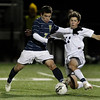 MARY SCHWALM/Staff photo. Windham's James Biguay holds off Hollis Brookline's Nate Rogers (11) as they challenge each other for the ball during the NHIAA Division II State Championship soccer game in Exeter.   11/4/12