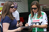 Ashley Force signs autographs at her team trailer.