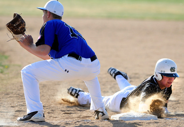 "Niwot High School's Tanner Morris (9) slides back to first base as Broomfield High School's Albert Garcia (15) waits for the throw during their game at Niwot High School on April 9, 2012.<br /> For more photos of the game go to  <a href=""http://www.bocopreps.com"">http://www.bocopreps.com</a><br /> Photo by Paul Aiken / The Camera"