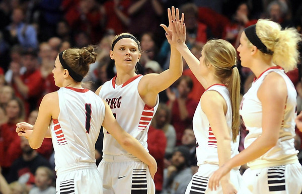 NRHEG's Carlie Wagner is congratulated by teammates after breaking the record for most points scored in the state tournament during the Class AA semifinal game against Howard Lake-Waverly-Winsted Thursday at Williams Arena. NRHEG won the game 87-58. Pat Christman