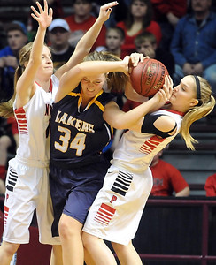 Howard Lake-Waverly-Winsted's Marissa Reed can't get out from between NRHEG's Anna Stork, left, and Gretchen Ramaker during the first half of the Class AA semifinal game Thursday at Williams Arena. Pat Christman