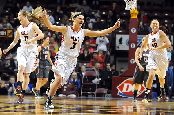New Richland-Hartland-Ellendale-Geneva's Anna Stork (11) Carlie Wagner (3) and Paige Overgaard (10) celebrate after defeating Kenyon-Wanamingo 71-61 to win the Class AA state girls basketball championship Saturday at Williams Arena. Photo by Pat Christman